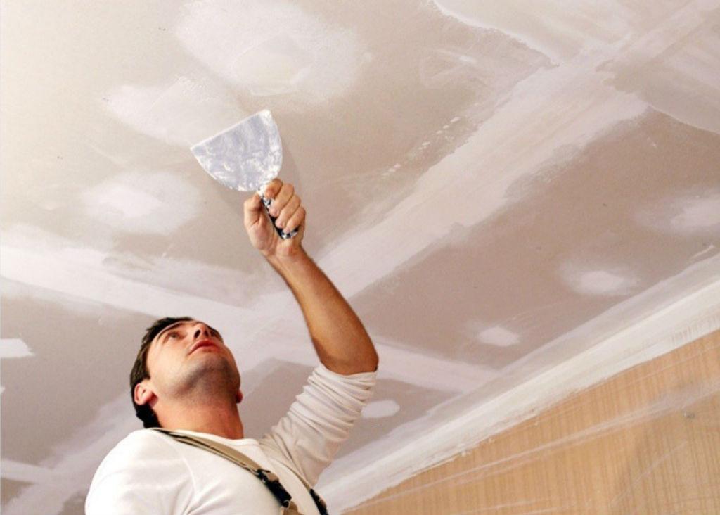 Мужчина замазывает шпаклевкой неровности и трещины в потолке