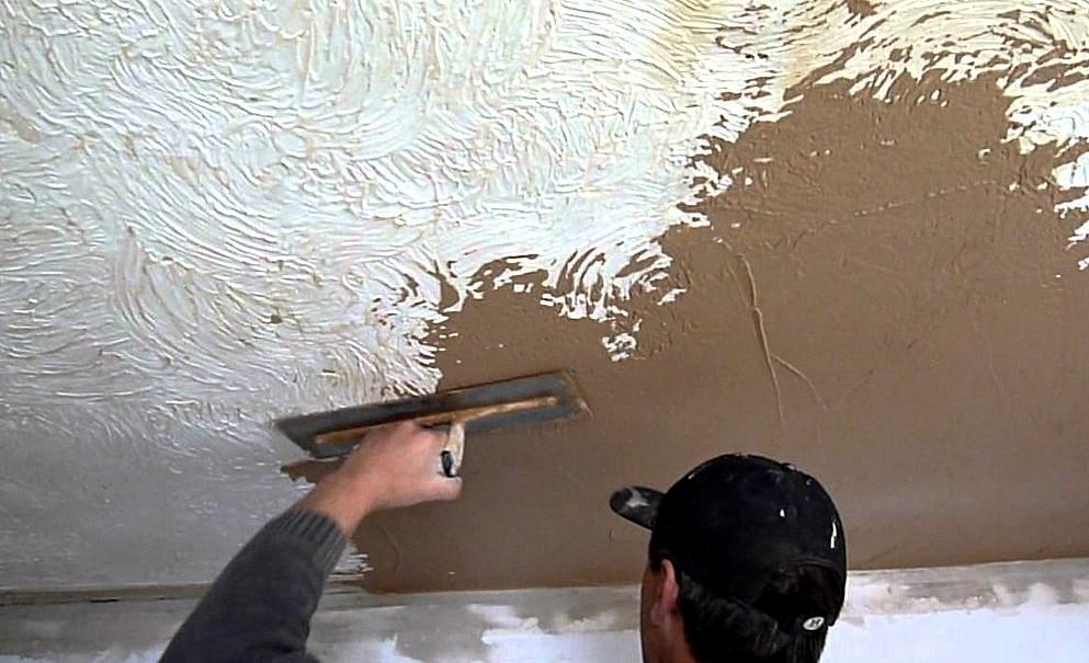 Рабочий с помощью кельмы наносит штукатурку на потолок